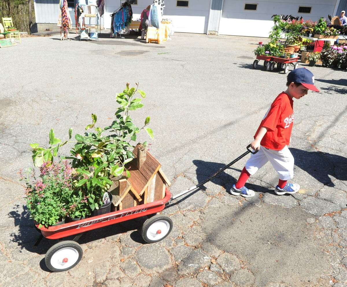 Axel Persson, then 6, of Old Greenwich, used a wagon to cart the flowers that his mother Laird Persson bought during the Garden Education Center of Greenwich annual May Gardeners Market at the center in the Cos Cob section of Greenwich, Conn., Saturday, May 2, 2015. Money raised from the event goes to support various community outreach programs according to the center's website.