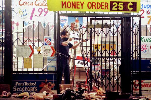 FILE - In this April 30, 1992 file photo, a Los Angeles police officer takes aim at a looter in a market at Alvarado and Beverly Boulevard in Los Angeles during the second night of rioting in the city.