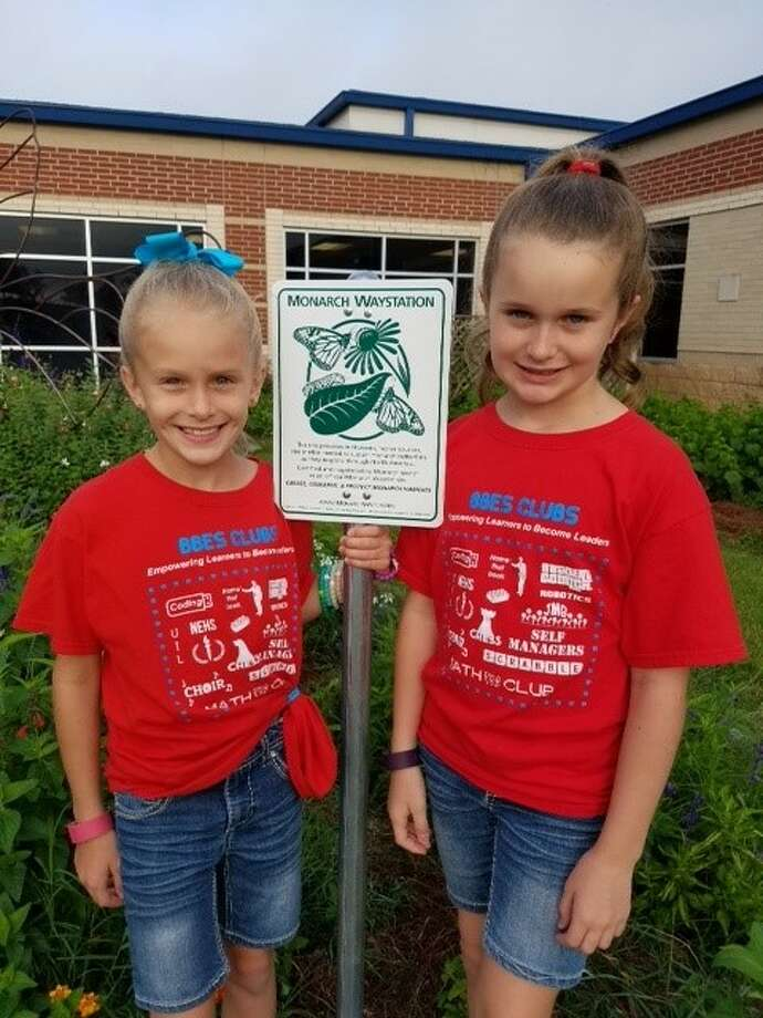 """Paisley and Hayley, JMG members, pose by the Monarch Waystation sign."""" Photo: Submitted Photo"""