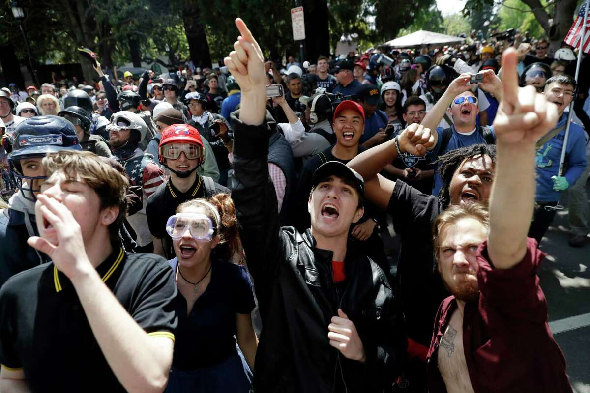 FILE - In this Thursday, April 27, 2017 file photo, demonstrators shout slogans directed at city hall during a rally for free speech in Berkeley, Calif. Ann Coulter didn't turn up in Berkeley on Thursday where hundreds held a raucous but largely peaceful demonstration in her absence and lamented what they called the latest blow to free speech in the home of America's free speech movement. (AP Photo/Marcio Jose Sanchez, File) ORG XMIT: FX105