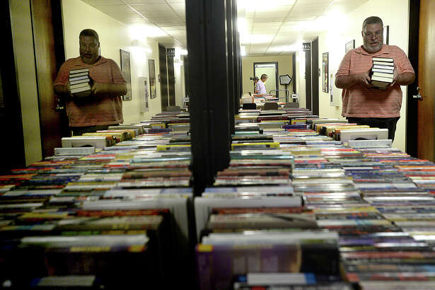 Members of Friends of the Beaumont Library and volunteers, including Rick Beaulieu, continue to sort and stack tables filled with books, videos, and books on tape as they prepare for the start of the Friends annual library book sale at the Main Branch in downtown Beaumont Friday. The event opens Friday to members of the group from 5 - 9 p.m. A $10 membership fee can be paid at the door for those wishing to join in the opening night of the sale. The sale continues free to the public Saturday from 9 a.m. - 4 p.m. All items are 10 cents, and there are thousands of titles from all genres of reading materials available, as well as a children's section. Photo taken Friday, April 28, 2017 Kim Brent/The Enterprise