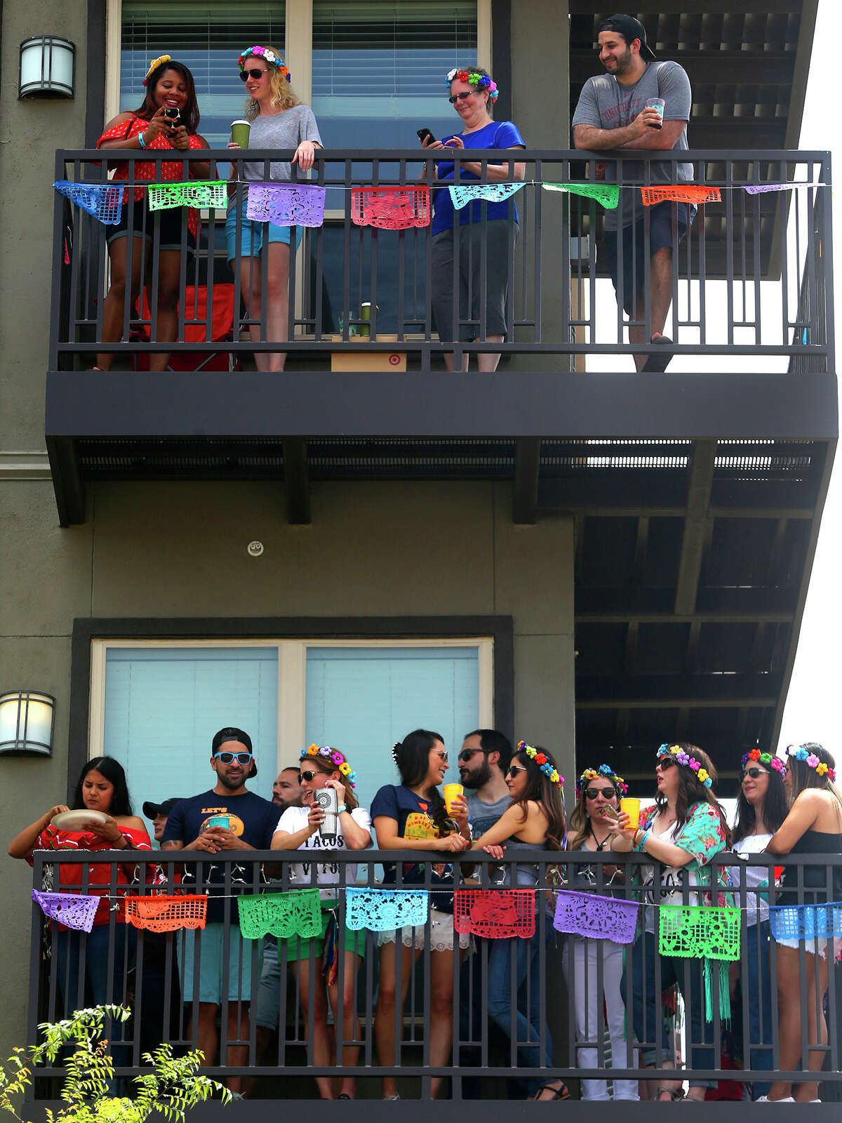 People celebrate the 2017 Battle of Flowers parade at apartment balcones on Broadway.