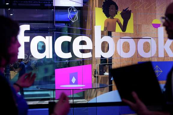 """FILE - In this April 18, 2017 file photo, conference workers speak in front of a demo booth at Facebook's annual F8 developer conference in San Jose, Calif.  In a paper posted online on Thursday, April 27, Facebook security researchers said the company will monitor the efforts of those who try to hurt """"civic discourse"""" on its service. It is also looking to identify fake accounts, and says it will notify people if their accounts have been targeted by cyber-attackers.  (AP Photo/Noah Berger)"""
