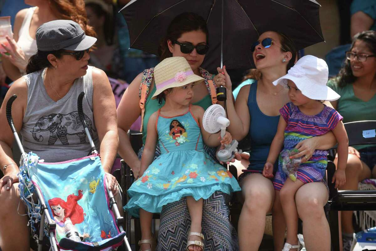 Children Milana and Mia Castillo keep cool by taking turns with a fan under the watchful eyes of Ruby Gutierrez, left, Gigi Gutierrez, middle rear, and Sofia Castillo during the Battle of Flowers Parade on Friday, April 28, 2017.