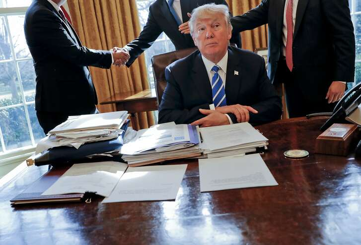 DAY 20 - In this Feb. 8, 2017, file photo. President Donald Trump sits at his desk after a meeting with Intel CEO Brian Krzanich, left, and members of his staff in the Oval Office of the White House in Washington. (AP Photo/Pablo Martinez Monsivais, File)