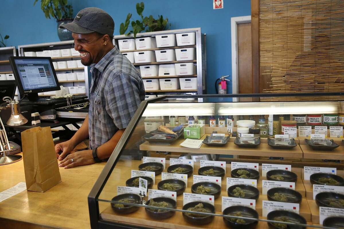 Bud tender Dustin Brown helps out a customer at Harborside Health Center medical cannabis dispensary May 12, 2016 in Oakland, Calif.