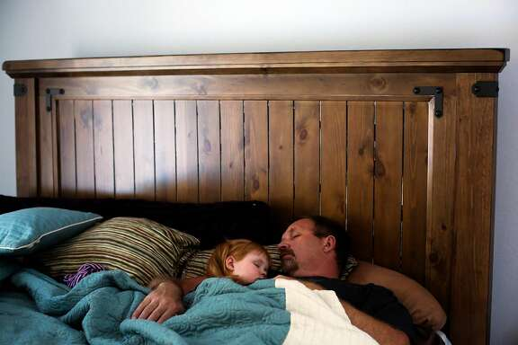 Brooke Adams, 3, takes a nap with her father Jon Adams after attending church in Santa Rosa, California, on Sunday, April 9, 2017. Brooke has Dravet's syndrome which causes severe epilepsy among other issues. She takes cannabis oil several times a day and when she has seizures. The cannabis oil significantly helps her condition.