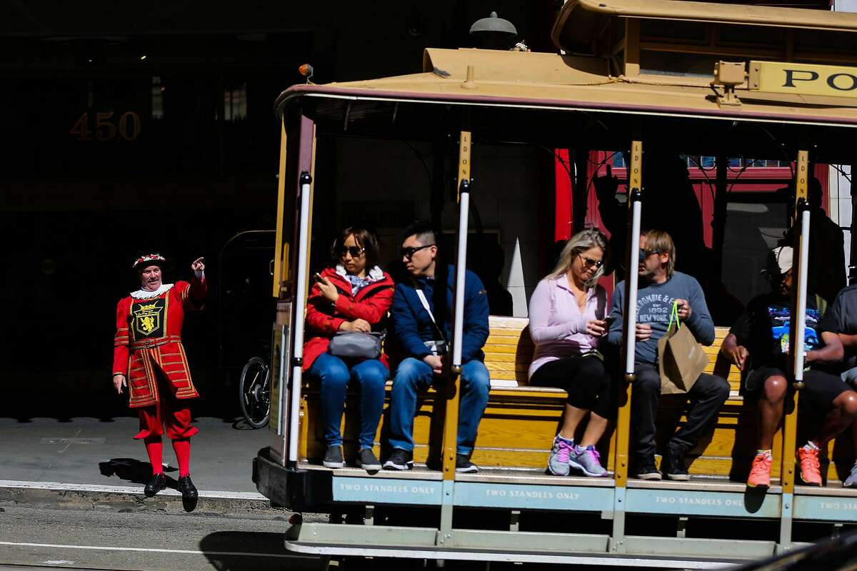 Sir Francis Drake hotel doorman Tom Sweeney greets a cable car as it rides past the hotel on Powell Street in San Francisco, California, on Thursday, April 27, 2017.