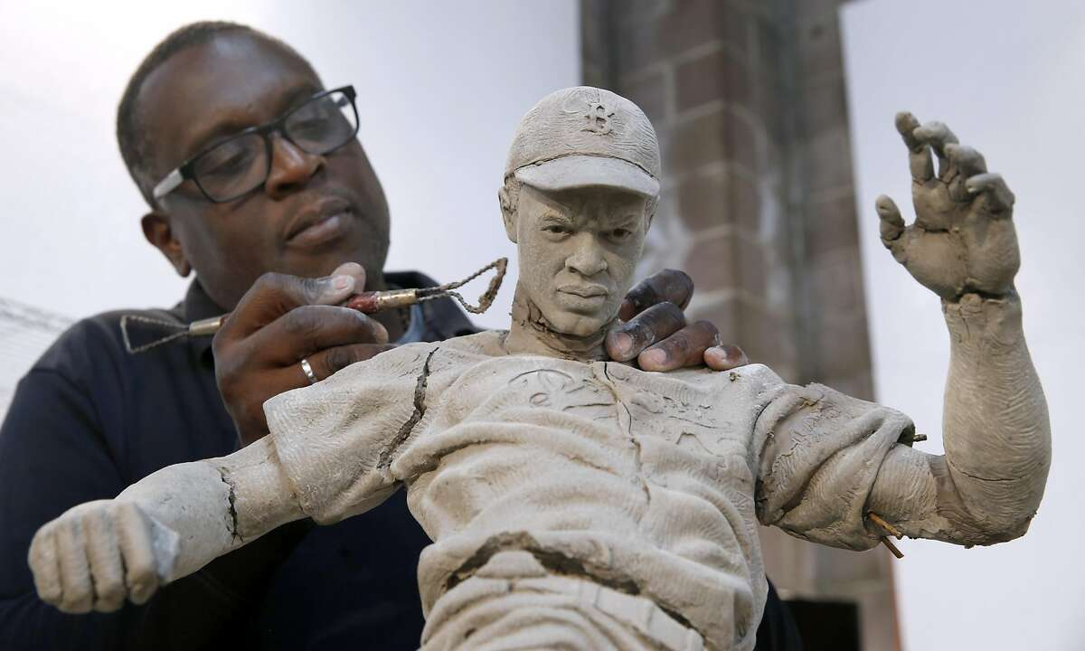 Branly Cadet repairs cracks in a maquette he used during the process of sculpting a Jackie Robinson statue at his studio in Oakland, Calif. on Wednesday, April 26, 2017. The Los Angeles Dodgers commissioned Cadet to sculpt a statue of Robinson stealing home plate which was unveiled at the beginning of the season outside of Dodger Stadium.