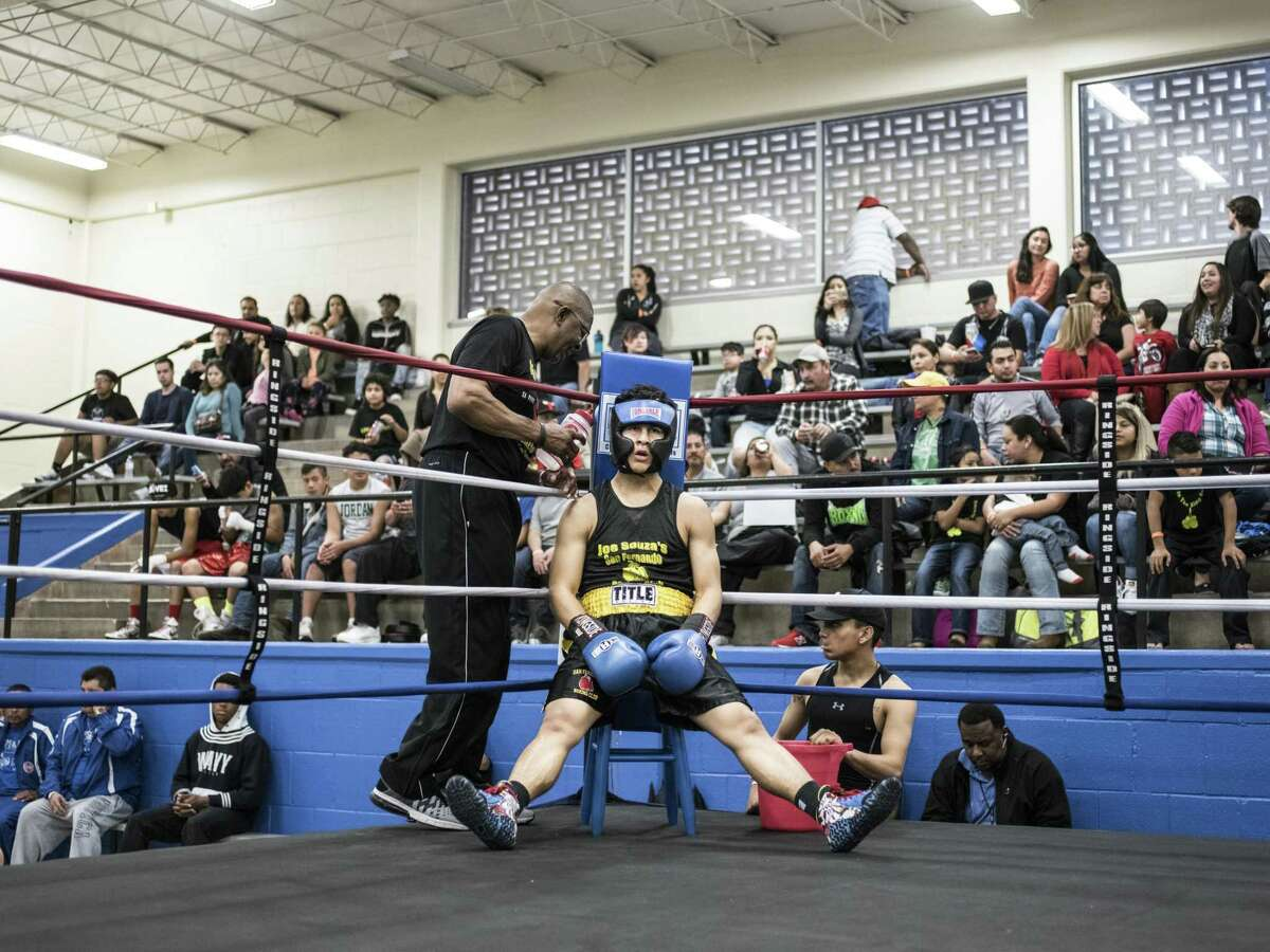 San Fernando Boxing Club coach Willie Hall, left, talks to his fighter Gerron Mena, in the corner during a boxing event at the Lincoln Community Center in San Antonio, Texas on Saturday, March 4, 2017.