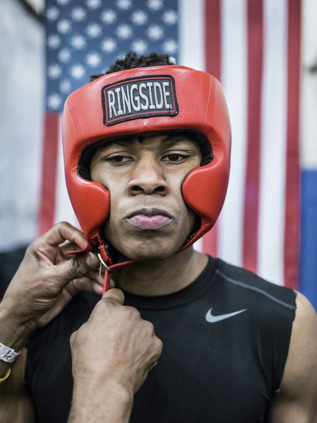 Joseph Barrow Jr., 20, from San Fernando Boxing Club, has his headgear put on before his first fight ever by longtime coach at San Fernando, Willie Hall, during a boxing event at the Lincoln Community Center in San Antonio, Texas on Saturday, March 4, 2017.