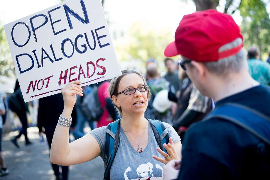 Anna Budd of Oakland speaks with a supporter of President Trump during a rally Thursday in Berkeley's Martin Luther King Jr. Civic Center Park. Photo: Noah Berger, Special To The Chronicle