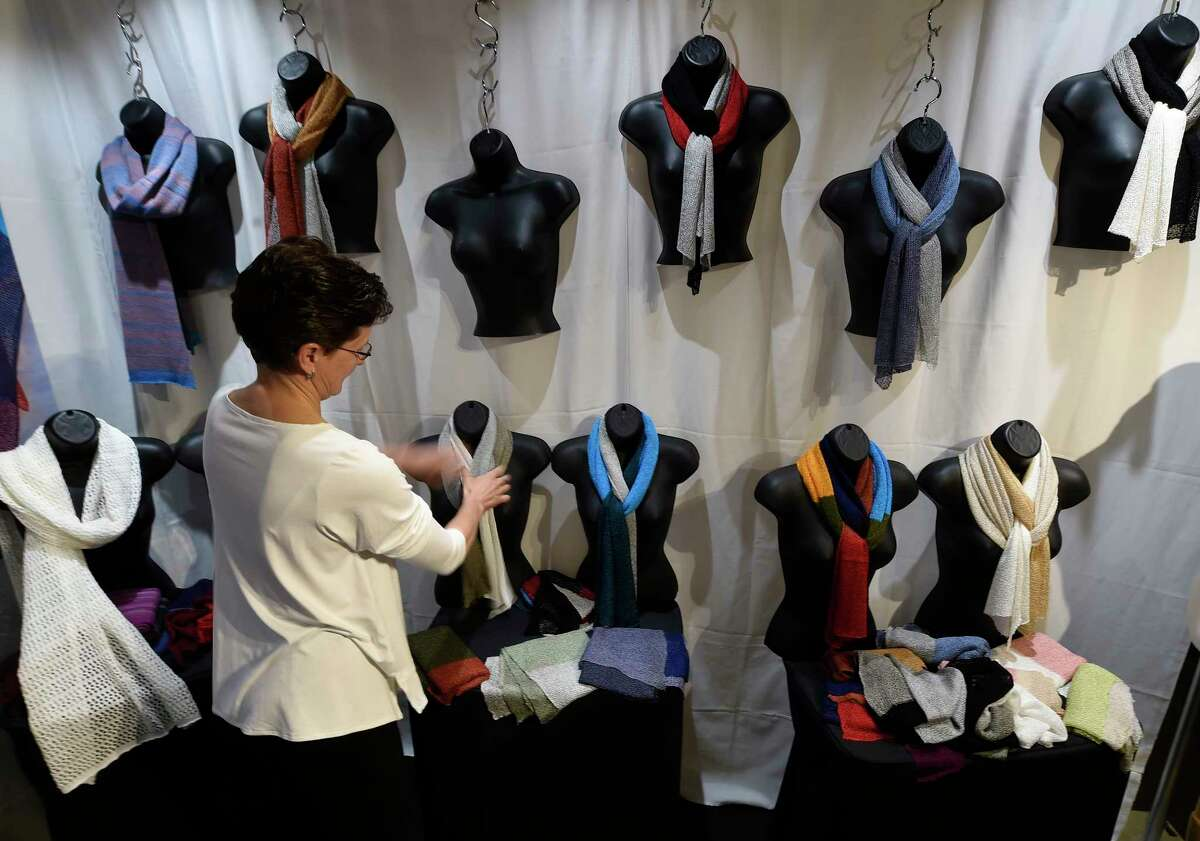 Lioubor Ermolova tidies up her display of knitwear as the Collar City Craft Fest opens at the Arts Center of the Capital Region Friday April 28, 2017 in Troy, N.Y. (Skip Dickstein/Times Union)