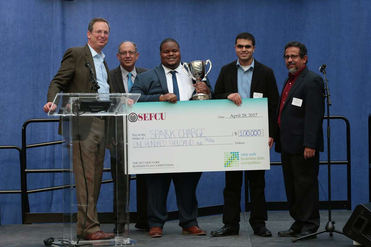 Syracuse University students Josh Aviv, center, and Jaydeep Sathe, center right, receive $100,000 for the first place finish of their company SparkCharge at the New York Business Plan Competition at SUNY Polytechnic Institute in Albany on Friday, April 28, 2017. Others in the photo are, from left, Peter Wohl of SEFCU and Hany Shawky, interim deal of the School of Business at the University at Albany. At far right is Pradeep Haldar, vice president of entrepreneurship innovation and clean energy programs at SUNY Poly's Colleges of Nanoscale Science and Engineering. ORG XMIT: eH9Vo1OjqeZu-_fNvNut