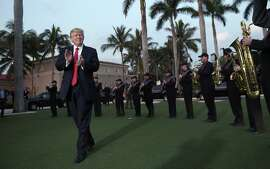 DAY 17 - In this Feb. 5, 2017, file photo, President Donald Trump listens to the Palm Beach Central High School Band as they play at his arrival at Trump International Golf Club in West Palm Beach, Fla. (AP Photo/Susan Walsh, File)