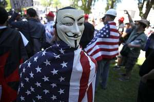 BERKELEY, CA - APRIL 27:  Right wing activists wear American flags during a rally at Martin Luther King Jr. Civic Center Park on April 27, 2017 in Berkeley, California. Protestors are gathering in Berkeley to protest the cancellation of a speech by American conservative political commentator Ann Coulter at UC Berkeley.  (Photo by Justin Sullivan/Getty Images)