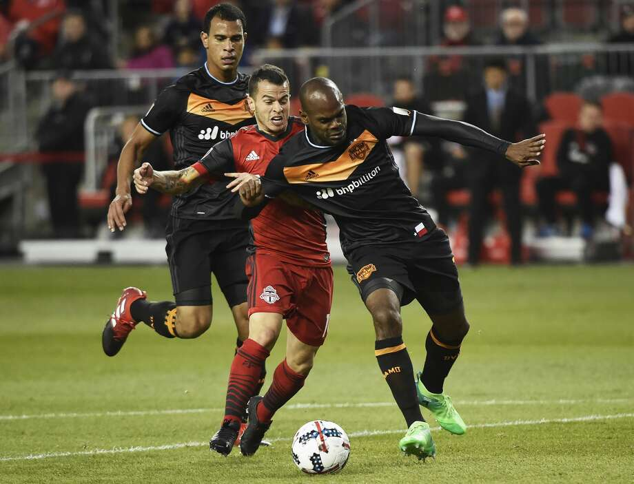 Toronto FC forward Sebastian Giovinco, middle, battles for the ball with Houston Dynamo defender Adolfo Machado, right, and midfielder Juan Cabezas during the first half of an MLS soccer match in Toronto on Friday, April 28, 2017. (Nathan Denette/The Canadian Press via AP)/The Canadian Press via AP) Photo: Nathan Denette/Associated Press