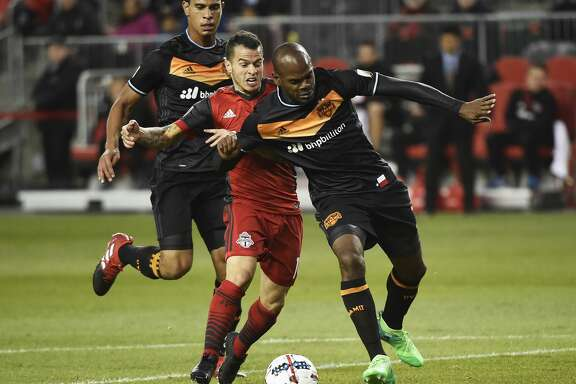 Toronto FC forward Sebastian Giovinco, middle, battles for the ball with Houston Dynamo defender Adolfo Machado, right, and midfielder Juan Cabezas during the first half of an MLS soccer match in Toronto on Friday, April 28, 2017. (Nathan Denette/The Canadian Press via AP)/The Canadian Press via AP)