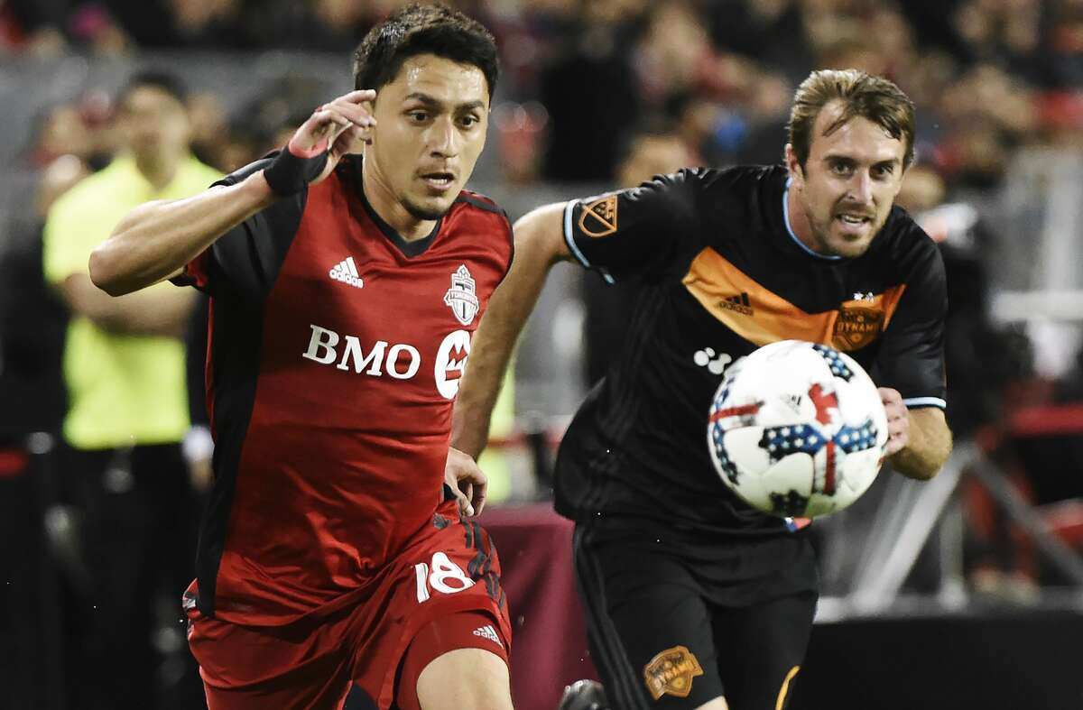 Toronto FC midfielder Marco Delgado (18) and Houston Dynamo midfielder Eric Alexander (6) chase the ball during the second half of an MLS soccer match in Toronto on Friday, April 28, 2017. (Nathan Denette/The Canadian Press via AP)