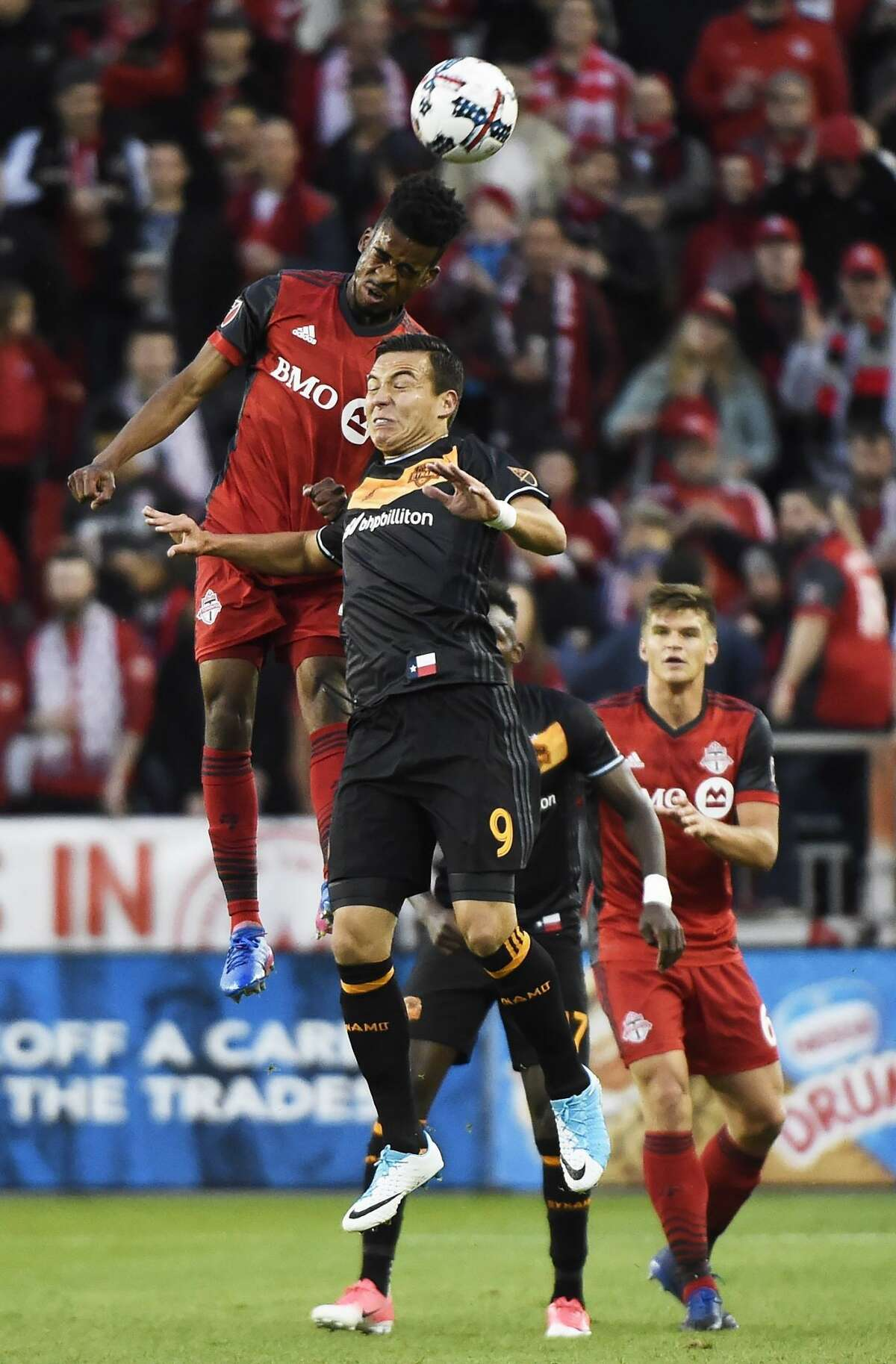 Toronto FC forward Raheem Edwards (44) and Houston Dynamo forward Erick Torres (9) jump for the ball during the first half of an MLS soccer match in Toronto on Friday, April 28, 2017. (Nathan Denette/The Canadian Press via AP)