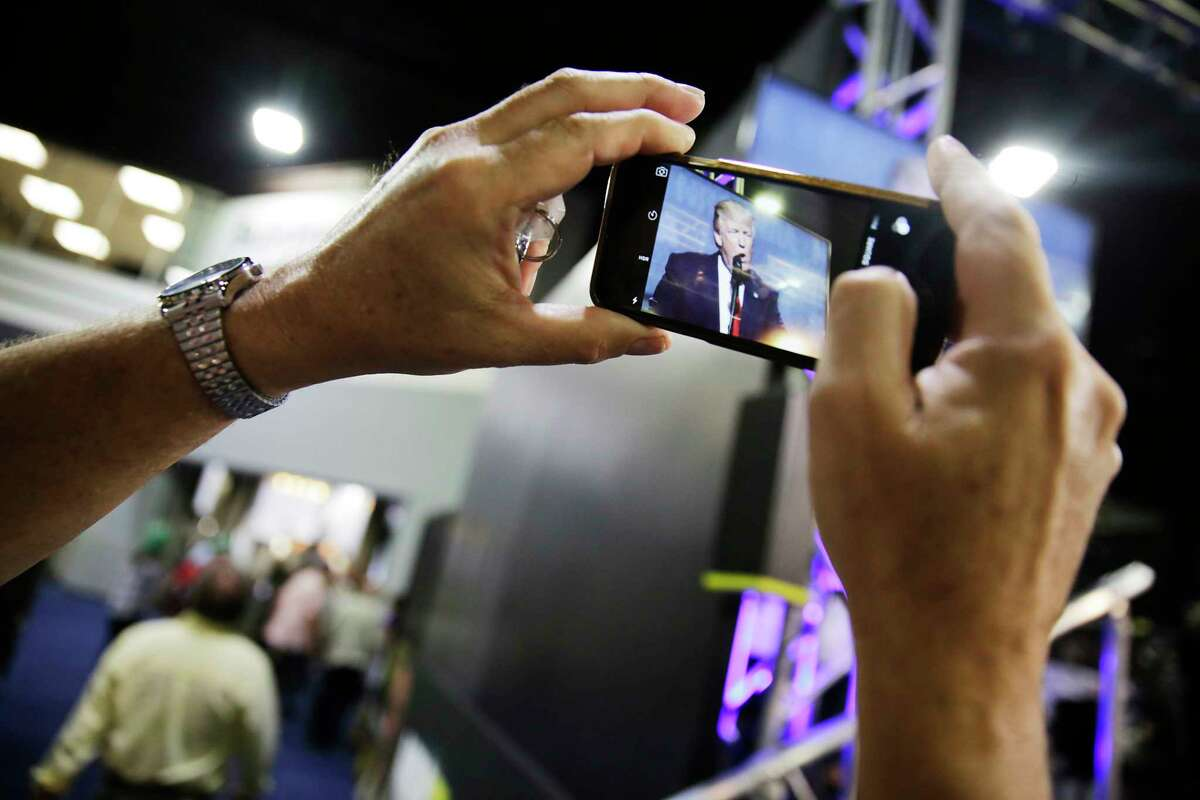 Alan Hasman, of Rochester, N.Y., takes a photo of a television in the exhibition hall broadcasting President Donald Trump speaking at the National Rifle Association's annual convention in Atlanta, Friday, April 28, 2017. (AP Photo/David Goldman) ORG XMIT: GADG119