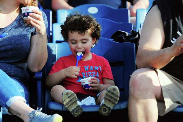 Massimo Carvalho, 3, of Fairfield, is a bit more interested in his ice cream than watching the game during the opening day of Bluefish baseball action against the Southern Maryland Blue Crabs at the Ballpark at Harbor Yard in Bridgeport, Conn., on Friday Apr. 28, 2017.