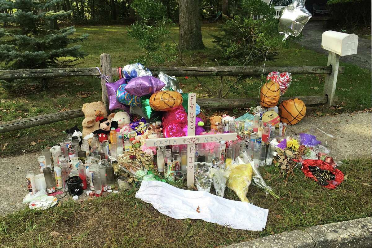 FILE - In this Sept. 27, 2016 file photo, a memorial to best friends Nisa Mickens and Kayla Cuevas is seen near the spot where their bodies were found in Brentwood, N.Y. Two suburbs on New York?'s Long Island are in the grip of fear from a violent street gang with Central American ties, MS-13. The gang has been blamed for the deaths of nearly a dozen young people in blue-collar Brentwood and Central Islip since the school year began. (AP Photo/Claudia Torrens, File) ORG XMIT: NYR201