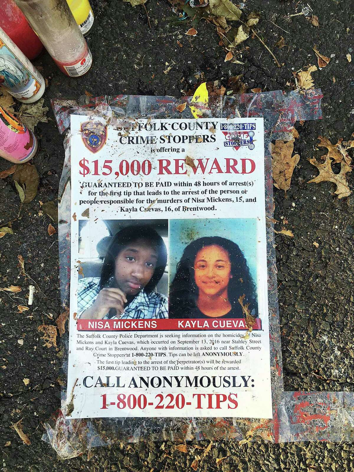 FILE - In this Sept. 27, 2016 file photo, a poster featuring photos of Nisa Mickens and Kayla Cuevas is part of a memorial near the spot where their bodies were found in Brentwood, N.Y. The girls, who were best friends, were found murdered. In the months leading up to her death, Kayla was involved in a series of disputes with members and associates of the MS-13, prosecutors said. (AP Photo/Claudia Torrens, File) ORG XMIT: NYR202