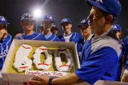 Oak Ridge coach Mike Pirtle is seen holding a celebratory cake after winning his 600th game.   is seen after the War Eagles defeated Montgomery 8-0 for Pirtle's 600th career win, Friday, April 28, 2017, in Oak Ridge.