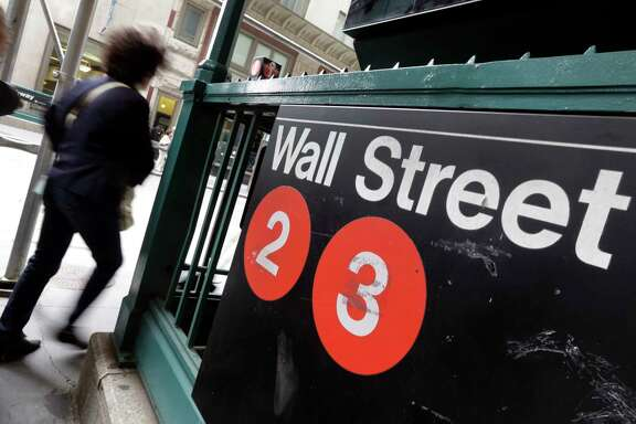 FILE - In this Oct. 2, 2014 file photo, people pass a Wall Street subway stop, in New York's Financial District.  The major U.S. stock indexes were mostly lower in early trading Friday, April 28, 2017,  as investors sized up the latest batch of company earnings.(AP Photo/Richard Drew, File)