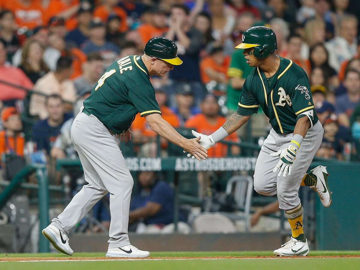 HOUSTON, TX - APRIL 28: Khris Davis #2 of the Oakland Athletics receives congratulations from third base coach Chip Hale #4 after hitting a home run in the third inning at Minute Maid Park on April 28, 2017 in Houston, Texas. (Photo by Bob Levey/Getty Images)