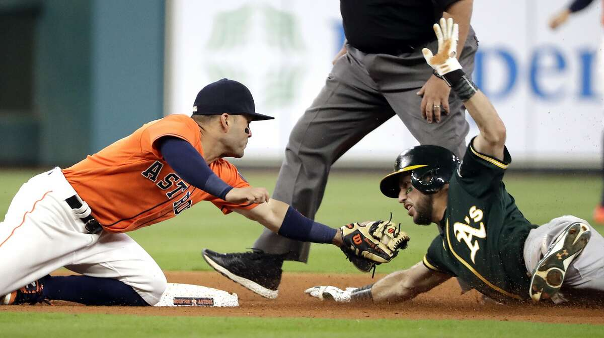 Oakland Athletics' Trevor Plouffe, right, is tagged out by Houston Astros second baseman Jose Altuve while trying to stretch a single into a double during the fourth inning of a baseball game Friday, April 28, 2017, in Houston. (AP Photo/David J. Phillip)