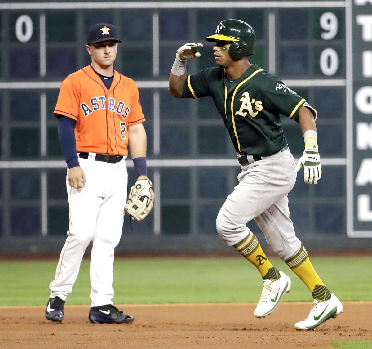 Oakland Athletics' Khris Davis, right, celebrates his three-run home run as he runs past Houston Astros third baseman Alex Bregman (2) during the first inning of a baseball game Friday, April 28, 2017, in Houston. (AP Photo/David J. Phillip)