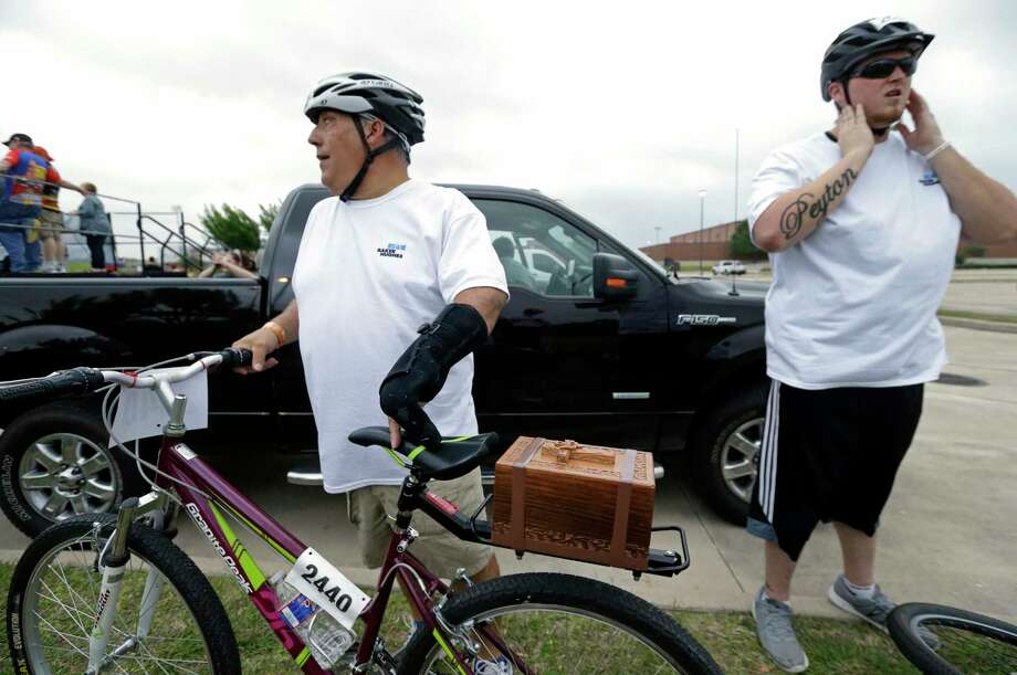 Michael Guillory, left, is shown with the cremation box of his late wife, Keri Guillory, attached to back of a bicycle as he and her son, Blake Eberhardt, right, prepare to start the 33rd Annual BP MS 150 bike ride at Tully Stadium, 1050 Dairy Ashford Road, Saturday, April 29, 2017, in Houston.  Keri Guillory along with another cyclist, Craig Randall Tippit were killed March 25, 2017 while participating in a MS150 training ride. Photo: Melissa Phillip, Houston Chronicle / © 2017 Houston Chronicle