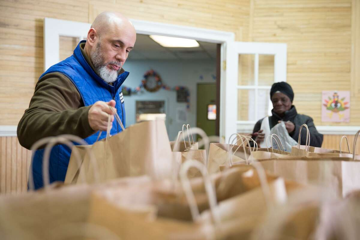 Open Door Shelter Director Frank Concepcion hands out a bag of non-perishable food at the Open Door Shelter in Norwalk, on Tuesday, Nov. 22, 2016. Area nonprofits are competing more for community foundation funding.