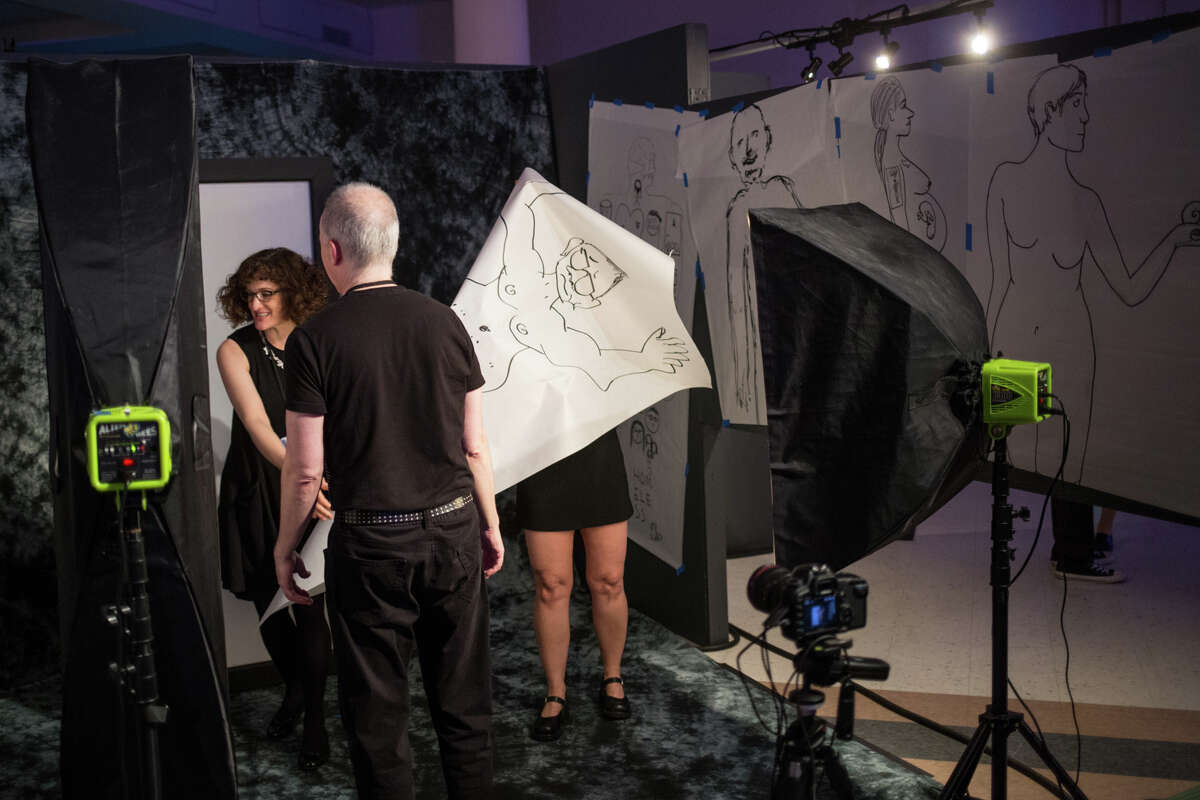 A booth at the Seattle Erotic Art Festival lets people draw and pose next to their drawing in the nude.