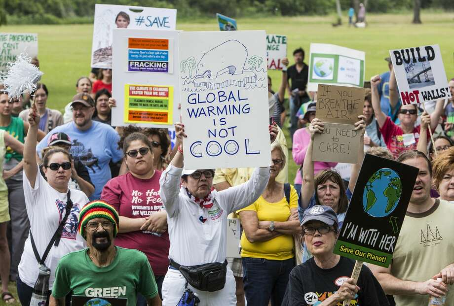 Demonstrators hold up signs while listening to speakers during the Houston Climate March rally at Clinton Park on Saturday, April 29, 2017, in Houston. ( Brett Coomer / Houston Chronicle ) Photo: Brett Coomer/Houston Chronicle
