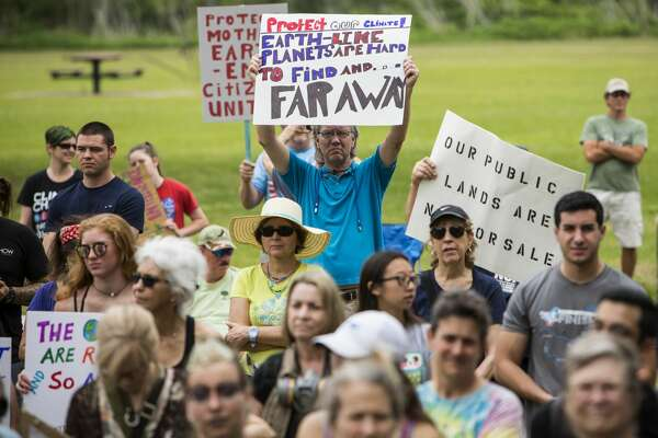 Demonstrators hold up signs while listening to speakers during the Houston Climate March rally at Clinton Park on Saturday, April 29, 2017, in Houston. ( Brett Coomer / Houston Chronicle )