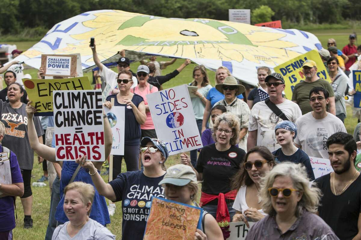 Demonstrators hold up signs and cheer while listening to speakers during the Houston Climate March rally at Clinton Park on Saturday, April 29, 2017, in Houston. ( Brett Coomer / Houston Chronicle )