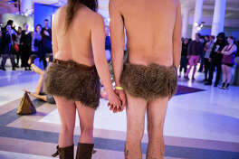 A couple dressed in loin cloths watches a partner yoga performance at the Seattle Erotic Art Festival at the Seattle Center Exhibition Hall on Friday, April 28, 2017.