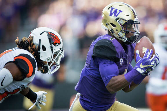 Washington wide receiver John Ross makes a reception while being tailed by Oregon State cornerback Treston Decoud in the first half of an NCAA football game at Husky Stadium on Saturday, Oct. 22, 2016.