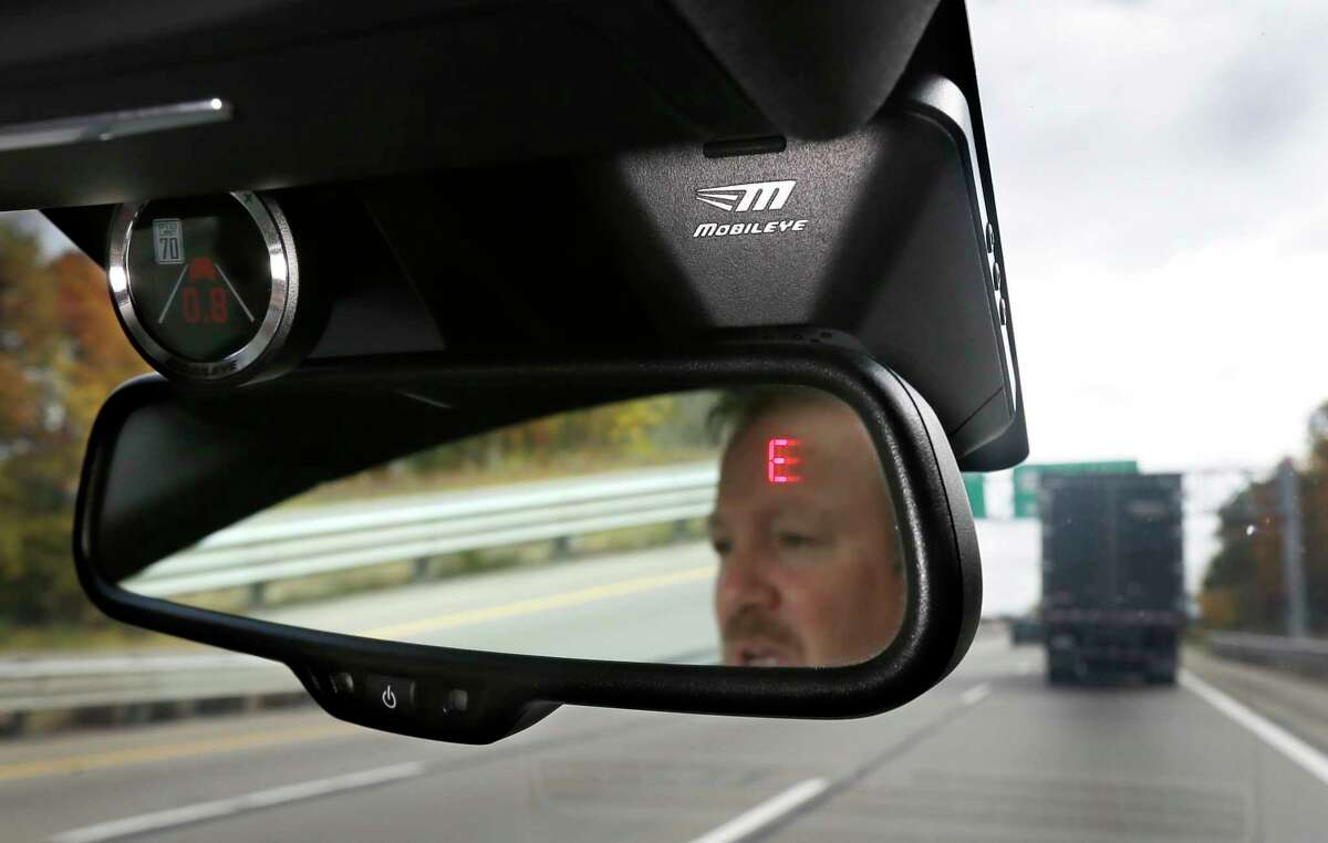 FILE - This Wednesday, Oct. 14, 2015, file photo shows a Mobileye camera system that can be installed in your car to monitor speed limits and warn drivers of potential collisions, mounted behind the rearview mirror during a demonstration of the system, in Ann Arbor, Mich. For a few hundred dollars, drivers can add new safety technology, like forward collision warning systems or backup cameras, to older cars. Cars are lasting longer than ever thanks to improving quality. The average U.S. vehicle is now 11.6 years old, according to the consulting firm IHS Markit. (AP Photo/Carlos Osorio, File) ORG XMIT: NYBZ502