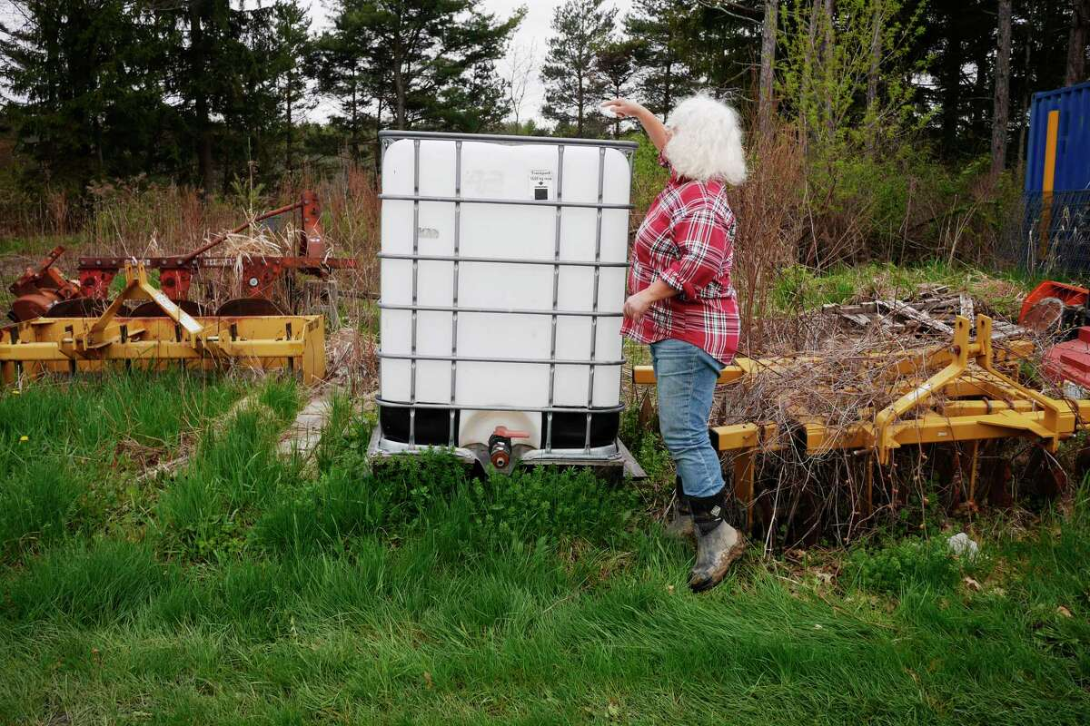 Rebekah Rice shows a 275-gallon water tank at 9 Mile Farm on Thursday, April 27, 2017, in Delmar, N.Y. Last summer when the irrigation pond on the farm ran down in the middle of August to a point where water could not be drawn out the water tank was transported to a neighbor's farm and filled every day and then brought back so the farm had water for the animals. They had to continue those daily trips from the second week of August through October. (Paul Buckowski / Times Union)