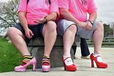 Jeff Geurin, left, of Waterford and Kevin Harris of Averill Park rest their feet before the start of the annual Walk a Mile in Her Shoes event Saturday April 29, 2017 in Troy, NY.  (John Carl D'Annibale / Times Union)