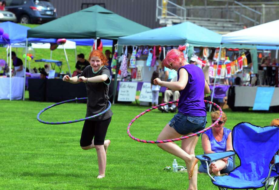 Casey Wilcock, left, and Jess Noe, play with hula hoops during Jonathan Law High School's annual festival: Peace Love & Music From Maren on the school's grounds in Milford, Conn., on Saturday Apr. 29, 2017. The festival celebrates the life of Sanchez, a student at the school who was fatally stabbed the day of her junior prom on April 25,2014. She was 16 years old. Some of the events included a kickball tournament, live music throughout the day, a mural and artwork gallery, bounce house fun for the kids and even food trucks. Photo: Christian Abraham / Hearst Connecticut Media / Connecticut Post