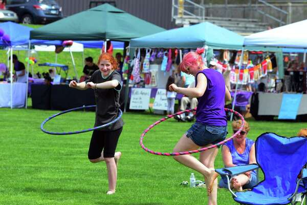Casey Wilcock, left, and Jess Noe, play with hula hoops during Jonathan Law High School's annual festival: Peace Love & Music From Maren on the school's grounds in Milford, Conn., on Saturday Apr. 29, 2017. The festival celebrates the life of Sanchez, a student at the school who was fatally stabbed the day of her junior prom on April 25,2014. She was 16 years old. Some of the events included a kickball tournament, live music throughout the day, a mural and artwork gallery, bounce house fun for the kids and even food trucks.