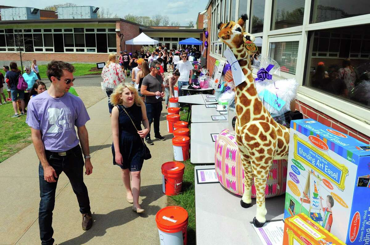 Andy Evanko and his girlfriend Natasha Knoblauch check out items for the silent auction during Jonathan Law High School's annual festival: Peace Love & Music From Maren on the school's grounds in Milford, Conn., on Saturday Apr. 29, 2017. The festival celebrates the life of Sanchez, a student at the school who was fatally stabbed the day of her junior prom on April 25,2014. She was 16 years old. Some of the events included a kickball tournament, live music throughout the day, a mural and artwork gallery, bounce house fun for the kids and even food trucks.