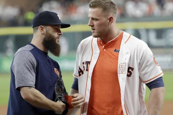 Houston Texans' J.J. Watt, right, talks with Houston Astros pitcher Dallas Keuchel after throwing out the first pitch before the Astros' baseball game against the Oakland Athletics on Saturday, April 29, 2017, in Houston. (AP Photo/David J. Phillip)