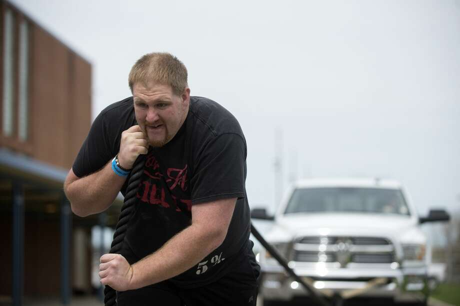 Luezern Dickson of Caro pulls a Ram 2500 during the pull-a-truck competition Saturday afternoon at Bullock Creek High School. Dickson pulled the truck weighing 10,000 pounds to the finish line in 1 minute 52 seconds. This is the 3rd annual Spring Natural and Fit day with more than 400 athletes competing in powerlifting, Brazilian Jiu-Jitsu, the pull a truck and the annual Michigan ROAR Natural Bodybuilding Championship. Photo: Brittney Lohmiller/Midland Daily News/Brittney Lohmiller