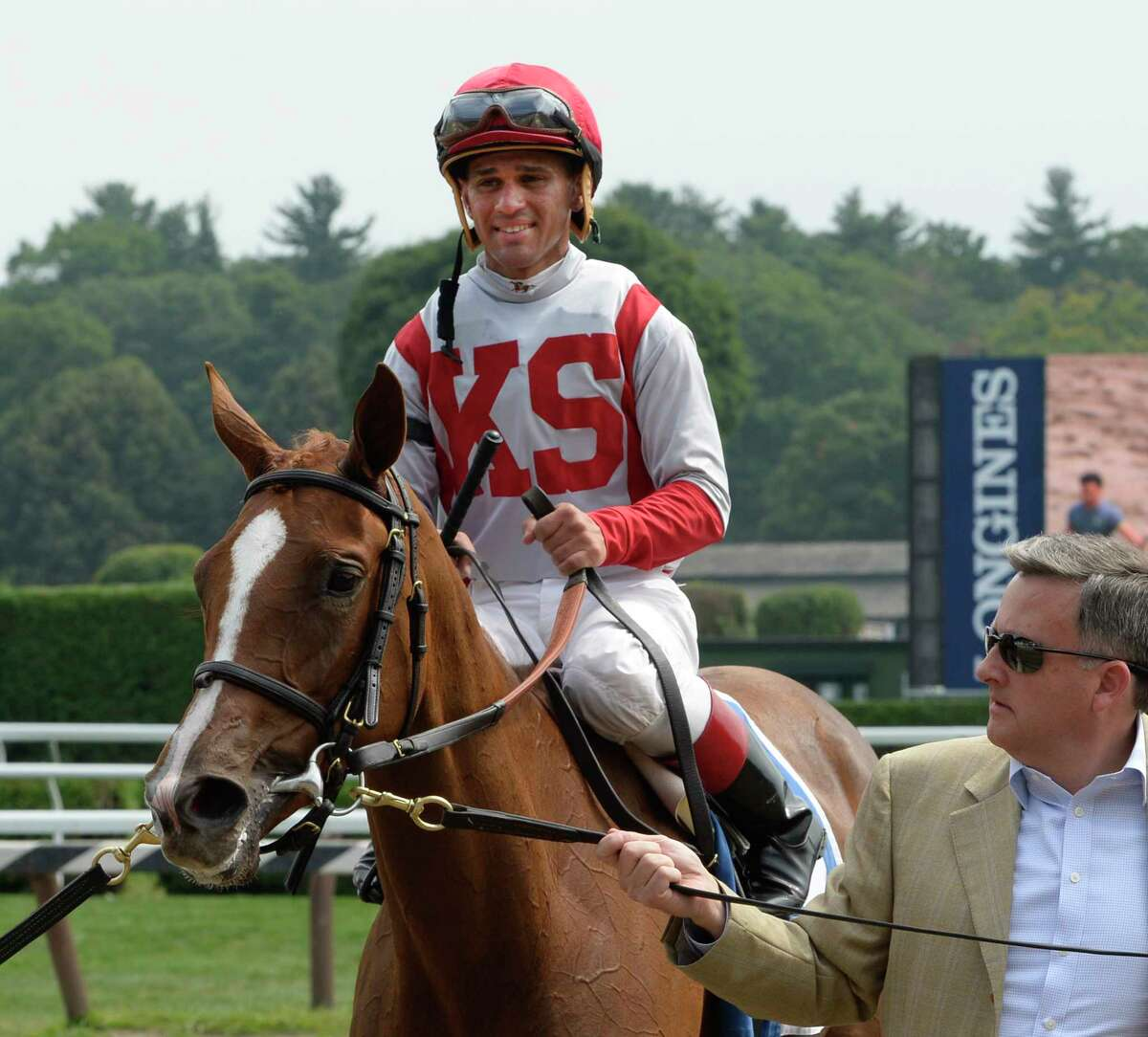 Partisan Politics with jockey Javier Castellano is lead to the winner's circle by co-owner William Lawrence after winning the 10th running of P.G. Johnson stake Wednesday afternoon at the Saratoga Race Course on Heritage Day Aug. 27, 2014 in Saratoga Springs, N.Y. Jockey Castellano won at least four races on the day. (Skip Dickstein/Times Union)